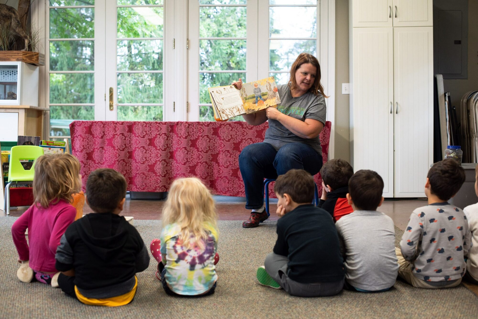 A photo of an environmental educator reading book to room of kids.
